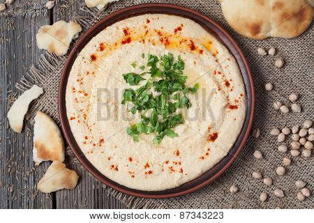 Bowl of hummus, creamy vegetarian food with chick-peas, paprika, olive oil and pita flatbread