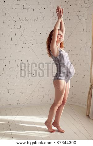 beautiful pregnant woman is doing morning exercises