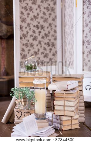 Old Book Heap And Candle In Vintage Interior Decoration