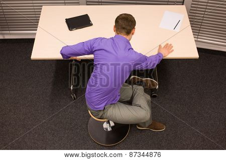 man exercising during short break in work at his desk in office