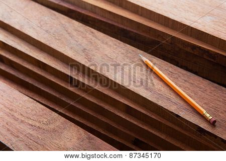 Hard wood lumber stacked with pencil on top. Wood working or interior carpentry.