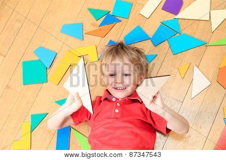happy little boy with puzzle toys on wooden floor