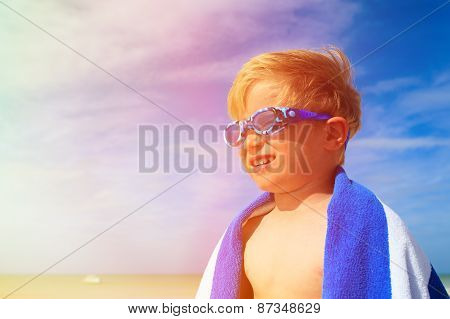 happy boy in swimming goggles on summer beach