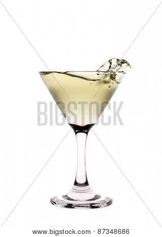 Yellow liquid splashing in a martini glass isolated on white background
