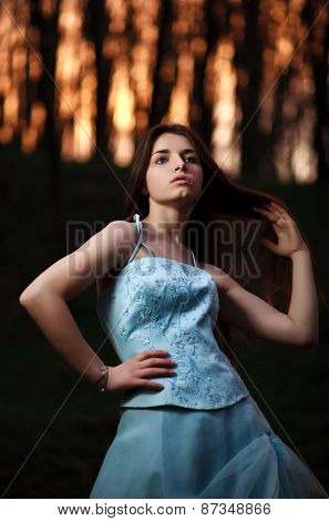 Young Girl In A Long Blue Dress Posing In A Dark Forest At Sunset