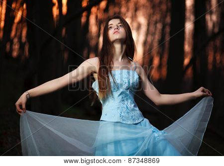 Young Girl In A Long Blue Dress Dancing In The Dark Forest At Sunset