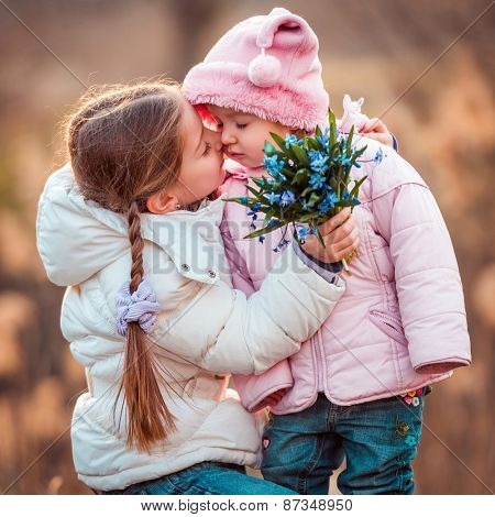 happy little girl kissing her sister and holding a bouquet of snowdrops
