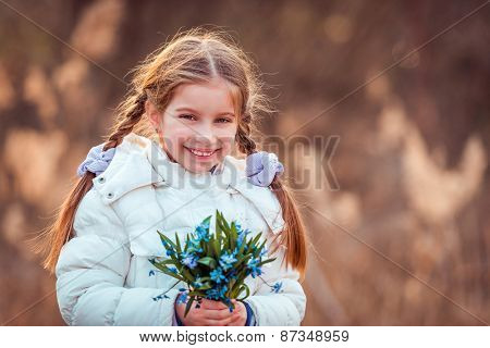 little girl smiling and holding a bouquet of blue  flowers