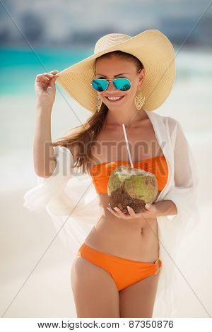 Beautiful lady in a bikini, removes thirst with coconut milk