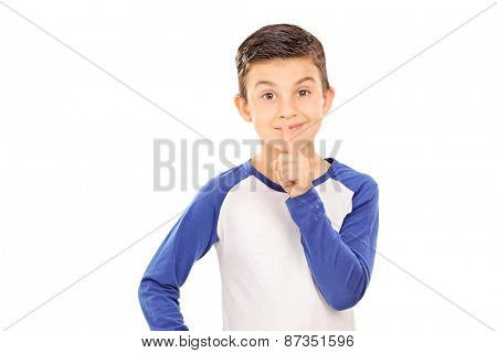 Cute little boy gesturing silence with his finger on his lips isolated on white background