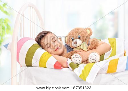 Lovely boy sleeping with a teddy bear in a comfortable bed covered with a striped multicolored blanket at home
