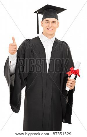 Proud young college graduate in a graduation gown holding a diploma and giving a thumb up isolated on white background
