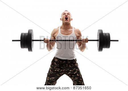 Determined young bodybuilder lifting a heavy barbell and screaming isolated on white background