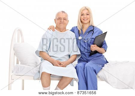 Female doctor hugging a mature patient seated in a hospital bed isolated on white background