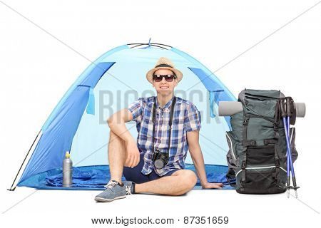 Studio shot of a male camper sitting in front of a blue tent with a backpack beside him isolated on white background