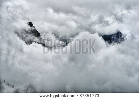 High And Steep Mountain Surrounded By Heavy Clouds