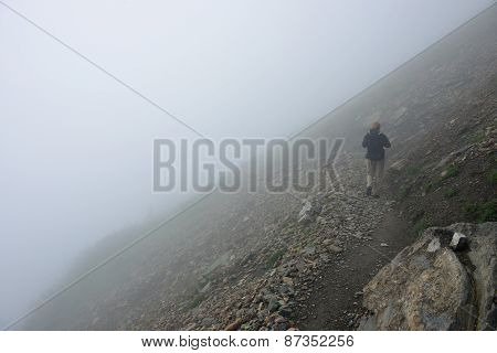 Female Hiker With A Backpack On A Highland Alpine Trail In Heavy Fog