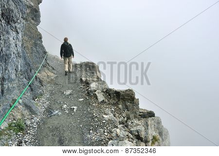Female Hiker With A Backpack On A Steep Highland Alpine Trail In Heavy Fog