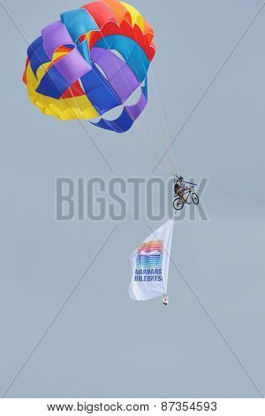 MARMARIS, TURKEY - APRIL 30, 2014: Parasailer on the bike with the flag of Marmaris municipality. This day the city met the 50th Presidential cycling Tour of Turkey
