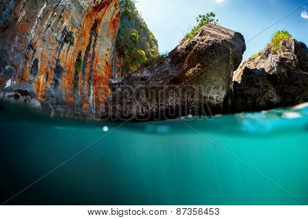 Underwater split shot with limestone mountains at sunny day