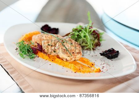White meat patty cakes with pumpkin mash on restaurant table