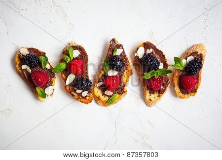Sweet berry bruschetta with chocolate nut butter,mint and sliced almonds