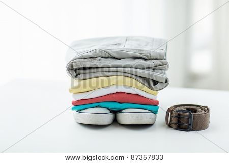 clothes, personal staff and objects concept - close up of folded shirts, pants, belt and shoes on table at home