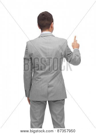 business, people, advertisement and office concept - businessman pointing finger or touching something imaginary from back
