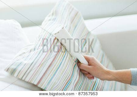 people, housework and housekeeping concept - close up of woman hand with sticky roller cleaning furniture textile or pillow