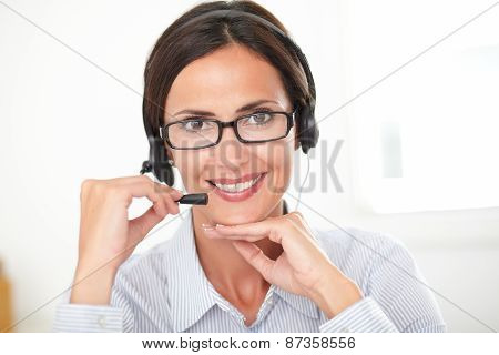 Hispanic Receptionist Conversing On Her Headphones