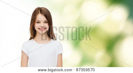 advertising, childhood, ecology and people - smiling little girl in white blank t-shirt over green background