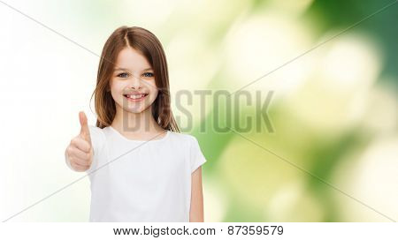 advertising, childhood, ecology and people - smiling little girl in white blank t-shirt showing thumbs up gesture over green background