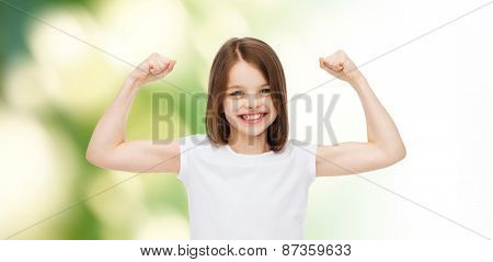 advertising, childhood, gesture, ecology and people - smiling little girl in white blank t-shirt with raised arms over green background