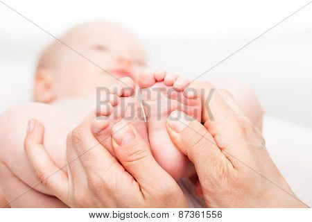 Close-up shot of three month baby girl receiving foot massage from a female massage therapist. Camera is focused on infant's feet. Face is blurred in background.