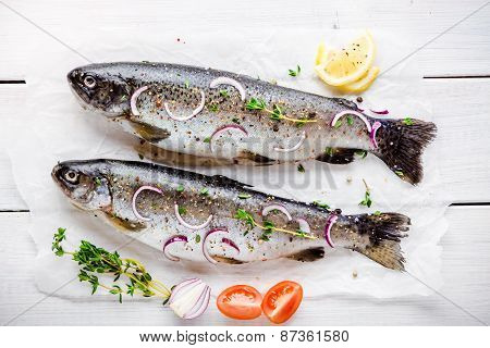 Two Raw trouts On Paper With Thyme And Red Onion Slices