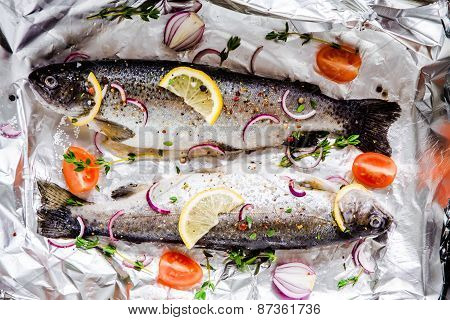 Two Raw River trouts With Thyme, Lemon, Red Onion And Tomatoes In Foil Closeup