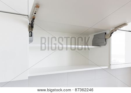 opened white kitchen cabinet with empty shelf