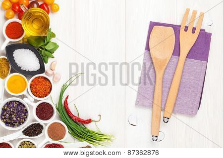 Various spices and kitchen utensil on white wooden background. Top view with copy space
