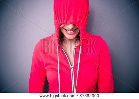 Portrait of a woman covering her eyes with hood over gray background
