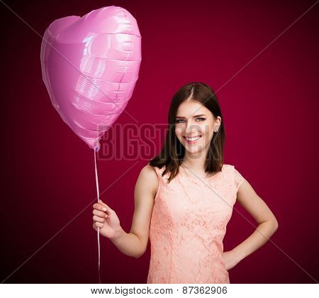 Smiling woman holding balloon over pink background and looking at camera