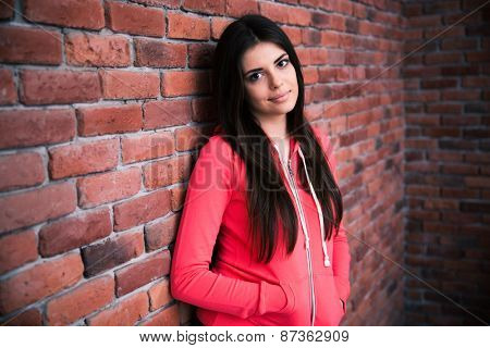 Portrait of attractive woman leaning on the brick wall and looking at camera