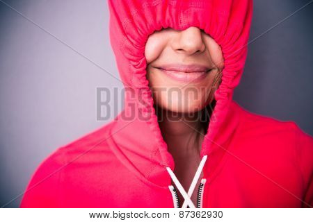 Portrait of a happy woman covering her eyes with hood over gray background