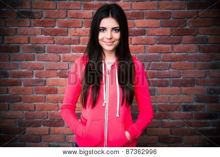 Portrait of a charming woman over brick wall. Looking at camera. Wearing in sports jacket