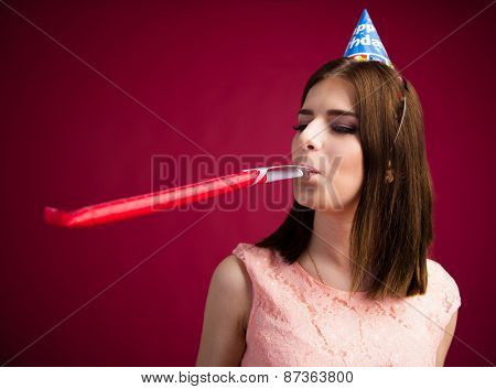 Young woman blowing in party whistle over pink background. Celebrating birthday.