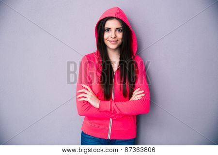 Happy young woman standing with arms folded over gray background. Looking at camera.