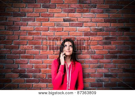 Young woman talking on the phone and looking up at copyspace over brock wall. Wearing sports jacket