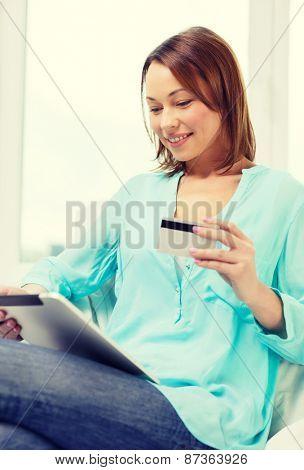 technology, banking, money, internet and home concept - smiling woman with tablet pc computer and credit card at home