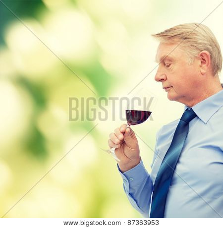 alcohol and beverage concept - elderly man smelling red wine