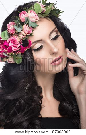 Portrait of a beautiful girl with a gentle make-up and lots of flowers in her hair. Spring image.