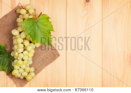 Bunch of white grapes on wooden table background with copy space